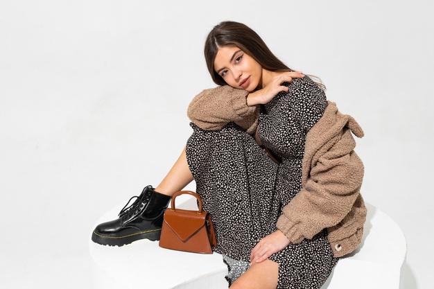 graceful-european-woman-winter-fur-coat-stylish-dress-sitting-wearing-ankle-boot-black-leather_273443-4014