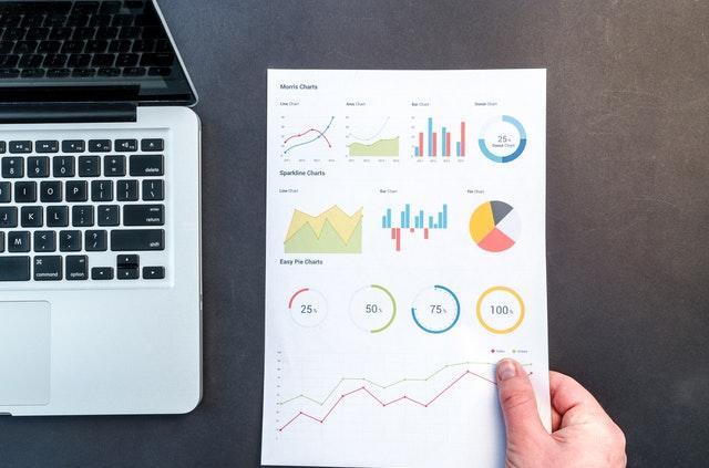 Notebook a človek, ktorý v ruke drží papier s rôznymi grafmi.jpg