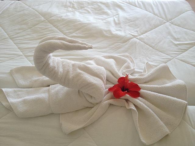 Labuť poskladaná z uteráku položená na bielom matraci.jpg