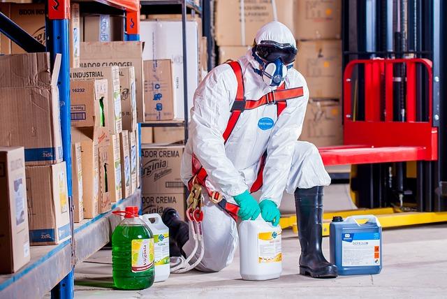 Muž v ochrannom obleku a maske pracuje s chemikáliami.jpg