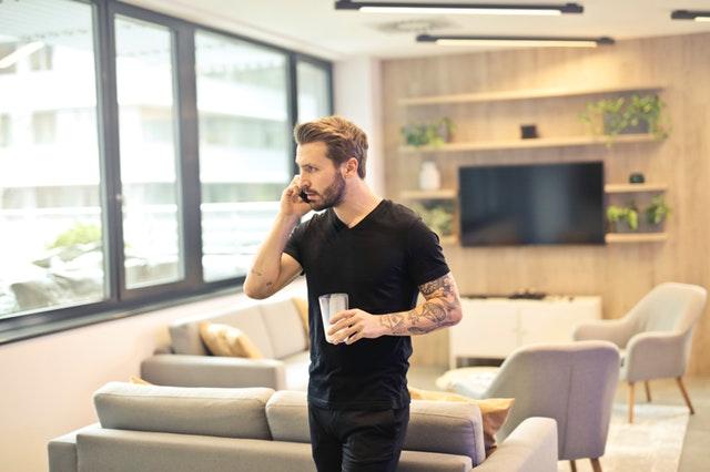 Muž v obývačke telefonuje a v ruke drží pohár.jpg